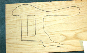 The swamp ash has been planed and the chambers are drawn onto the body blank