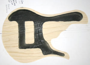 The swamp ash body core (bath tub) done with the body shape overlayed. The chamber is painted black to make the soundholes black in the final bass